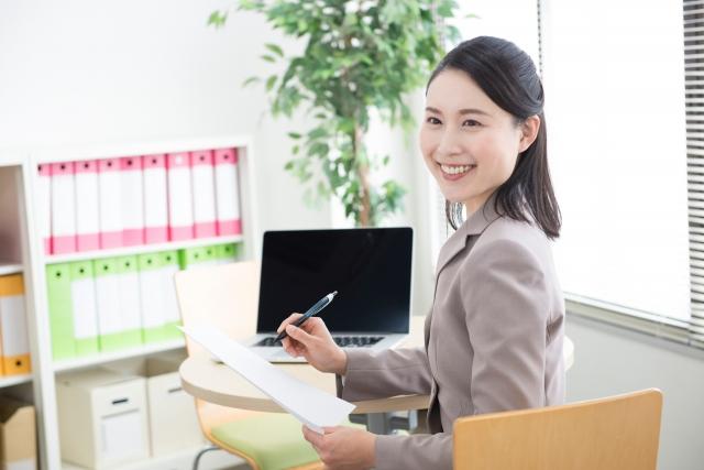 オフィスでノートPCを開いて働く女性