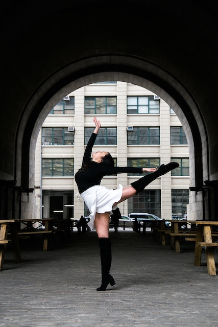 female dancer posing in front of a modern building